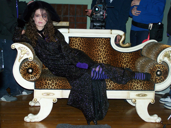 Sexy mean witch in sparkle robe and black hat laying on leopard print couch from short film F.L.U.S.H.E.D., costume design by Katharine Tarkulich