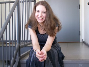Female costume designer sitting on stairs in gray and black dress